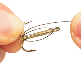 6.  Hold the second treble in place and carefully wrap the wire around the base of the hook like this.