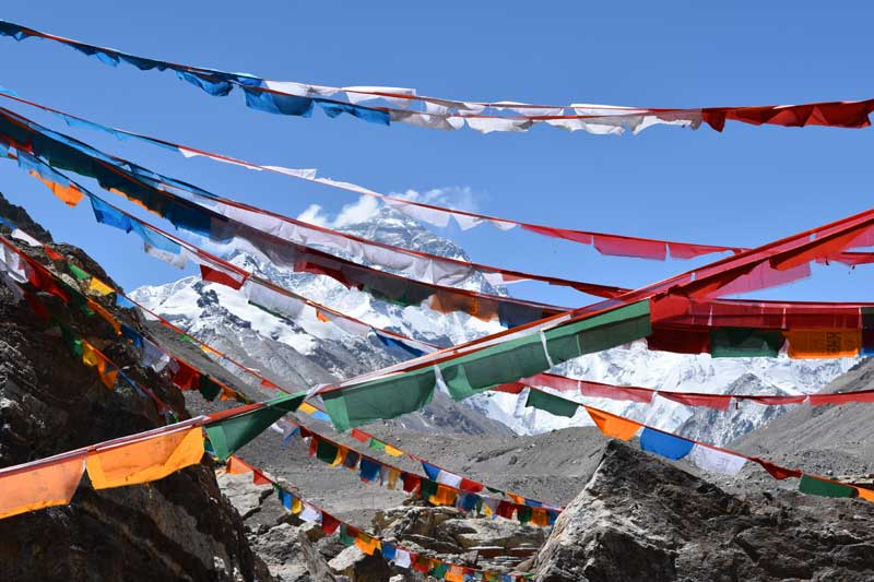 Everest summit looking through Tibetan prayer flags at the Rhombock Monastery. Image by Jon Gupta