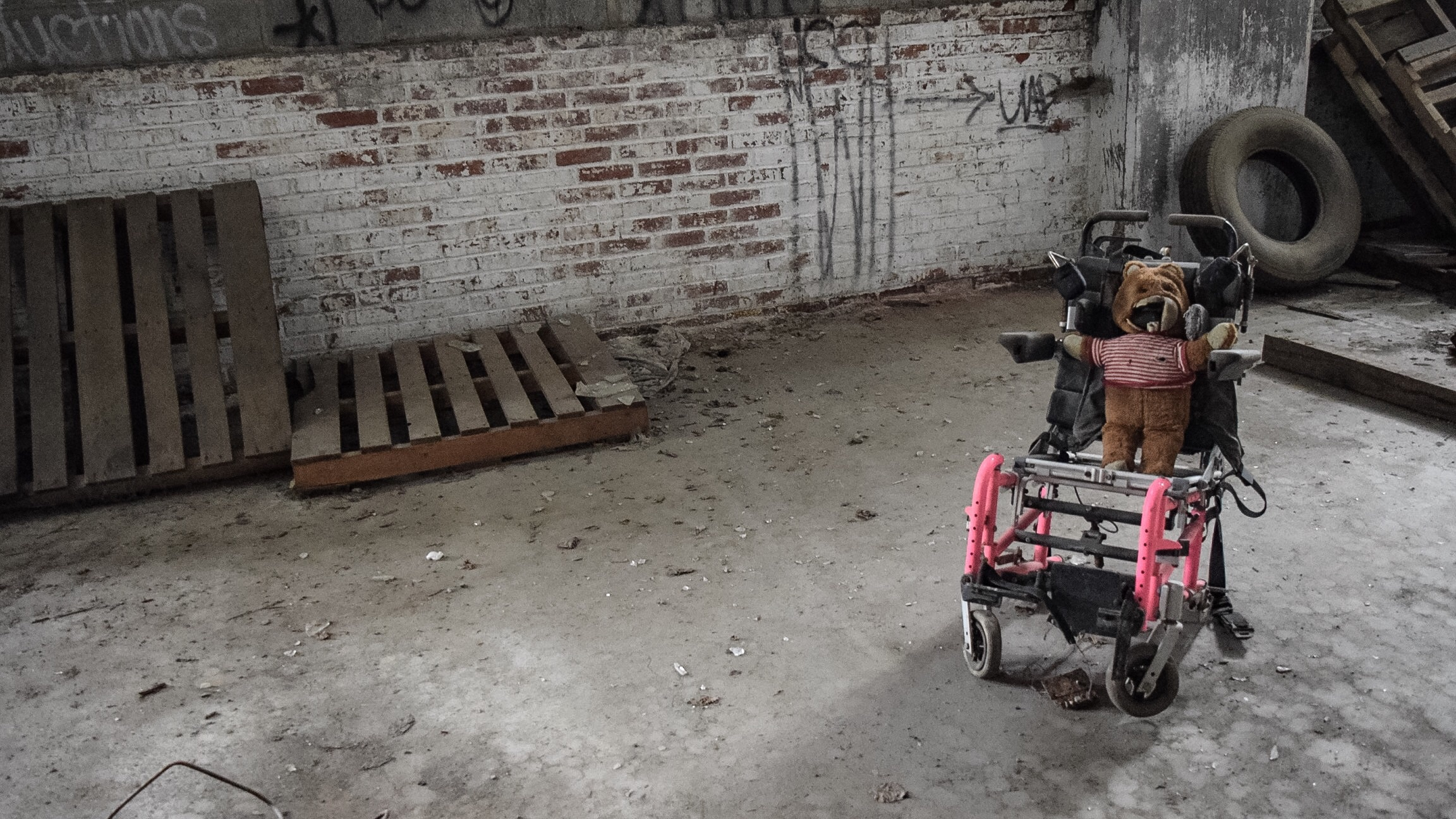 A disfigured teddy bear in a wheel chair.