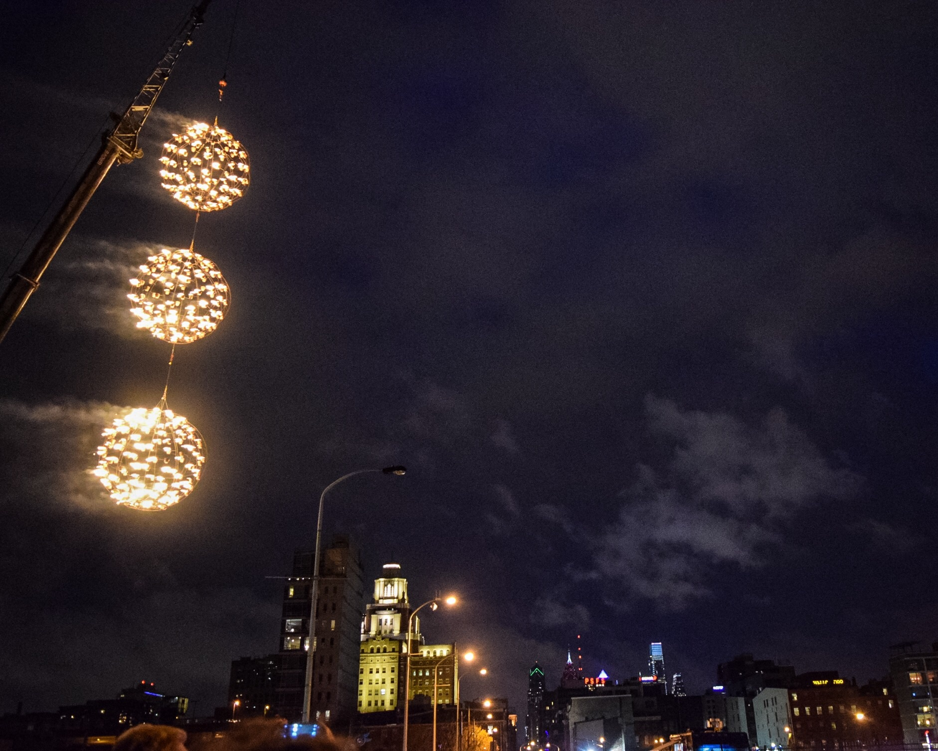 Three fiery globes burn above the entry to Penn's Landing and the  Article 13  installation.