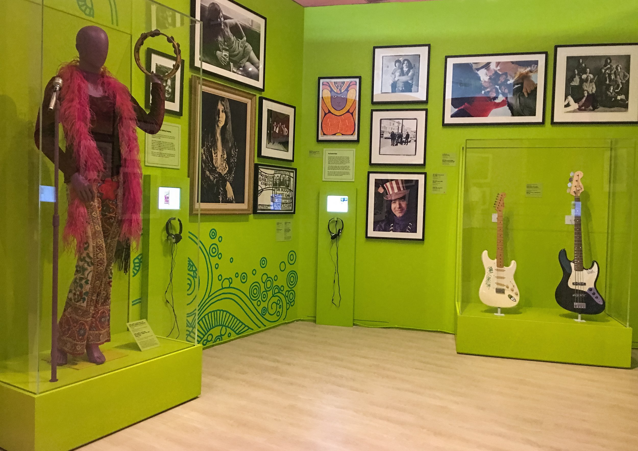 Janis Joplin stage outfit, mic stand, and tambourine across from a Jerry Garcia guitar and Phil Leah bass, celebrating Graham's relationship to two of music's most iconic acts.