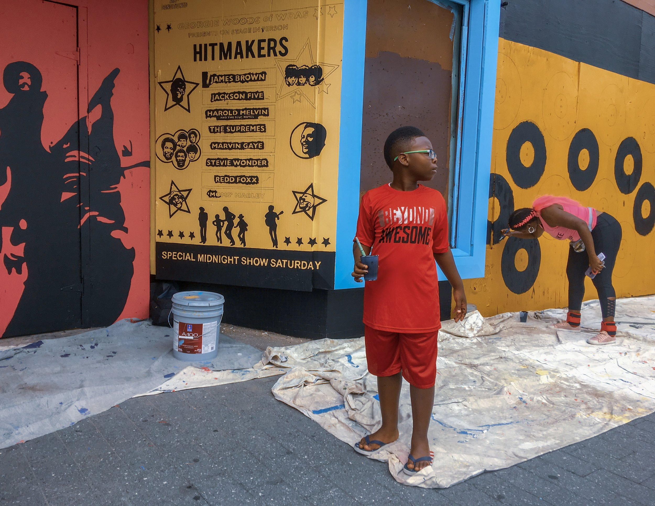 The Mural Arts Program invited the community to join in painting a new mural celebrating the Uptown Theater's golden era as part of the Chitlin Circuit in the 50s, 60s, and 70s.