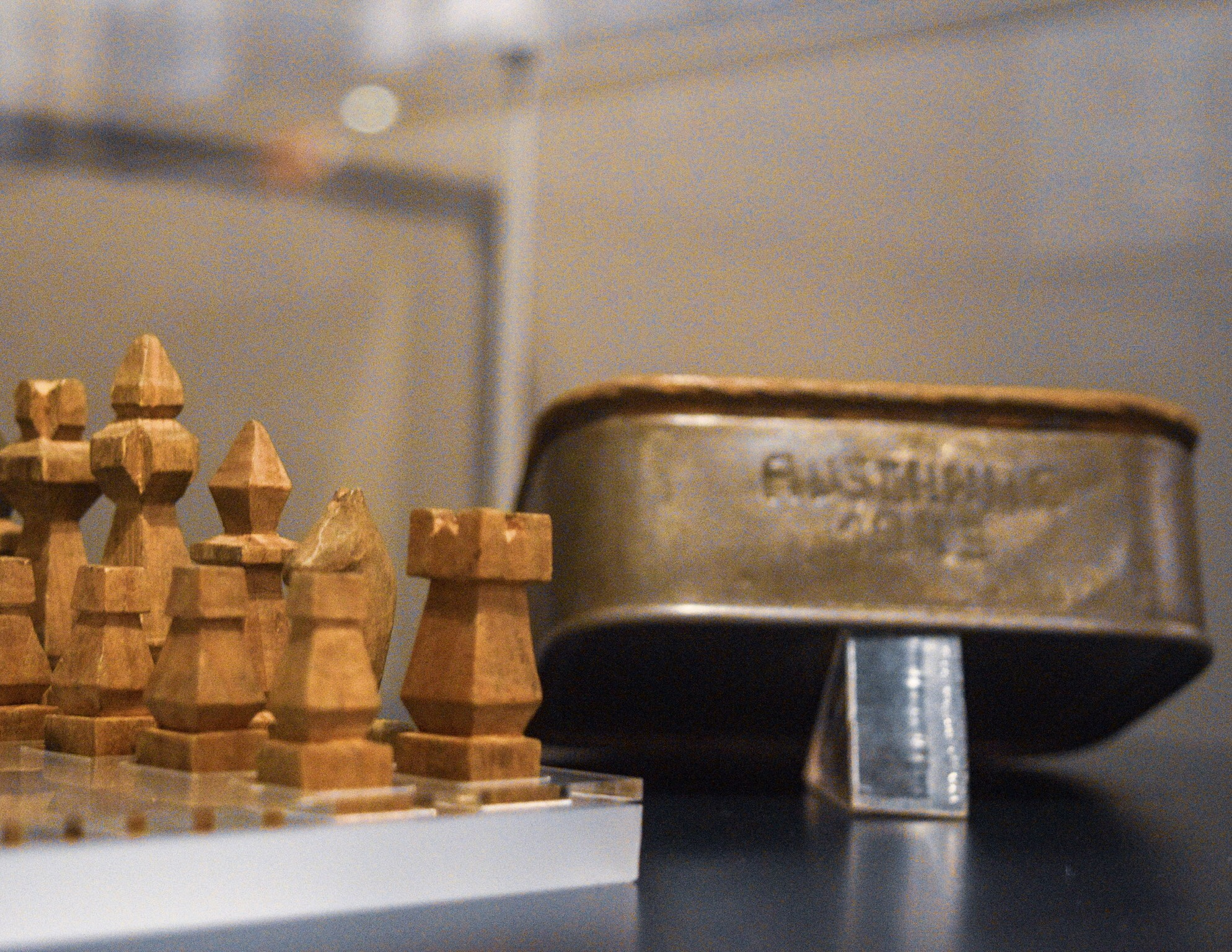 """Prisoner handmade chess set and sardine can case, with the word """"Auschwitz"""" carved into it."""