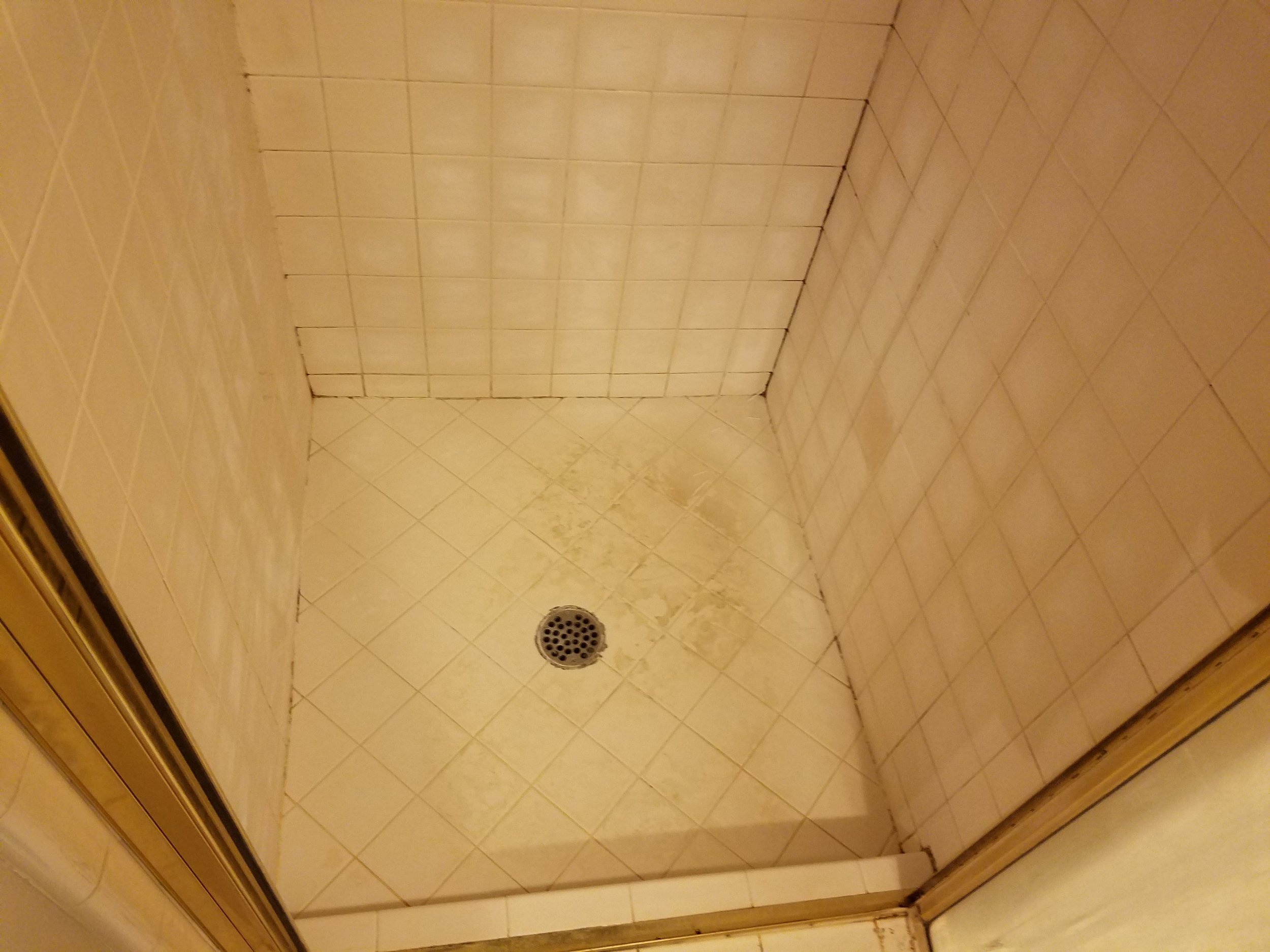 Notice the heavy soap scum build up on the walls and floor.