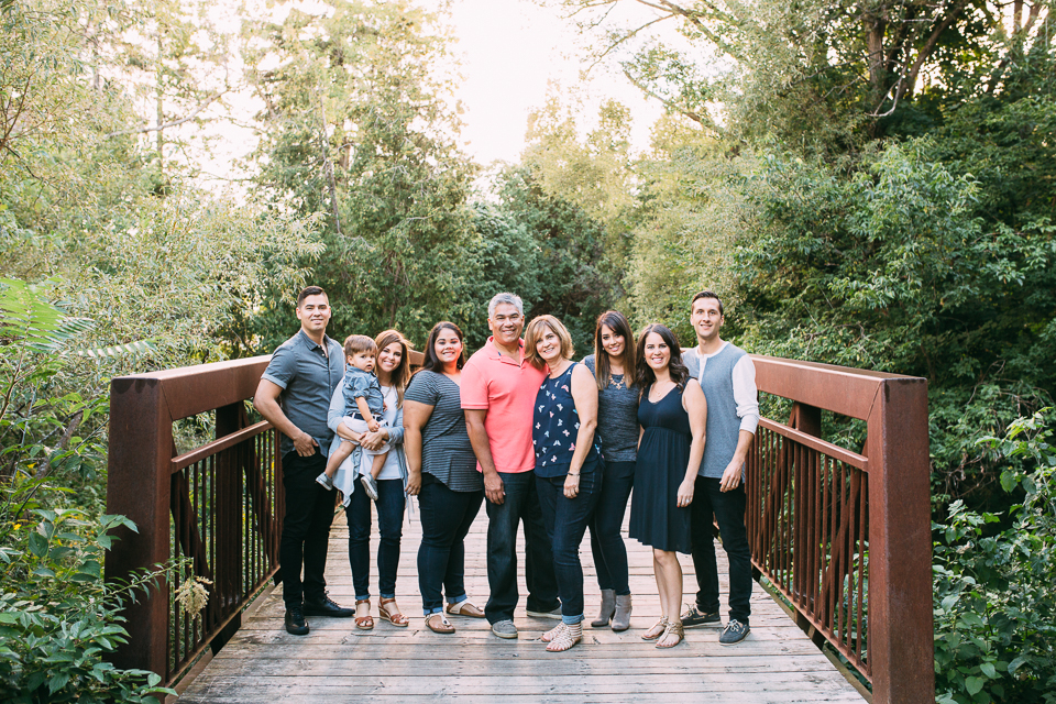 Extended family of 9 with 2 year old toddler boy standing on bridge smiling at camera - Stouffville family photography