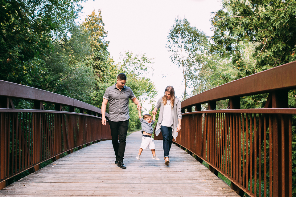 Family of 3 walking down bridge with 2 year old toddler boy swinging between mom and dad - Stouffville lifestyle photography