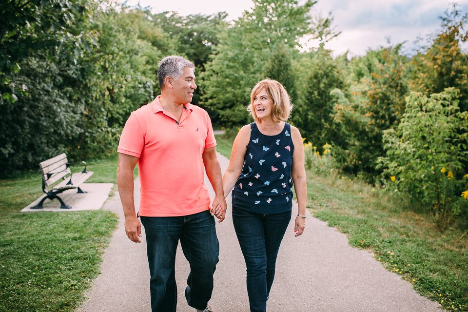 mature couple walks down park path holding hands wife smiling at husband - Newmarket lifestyle photography