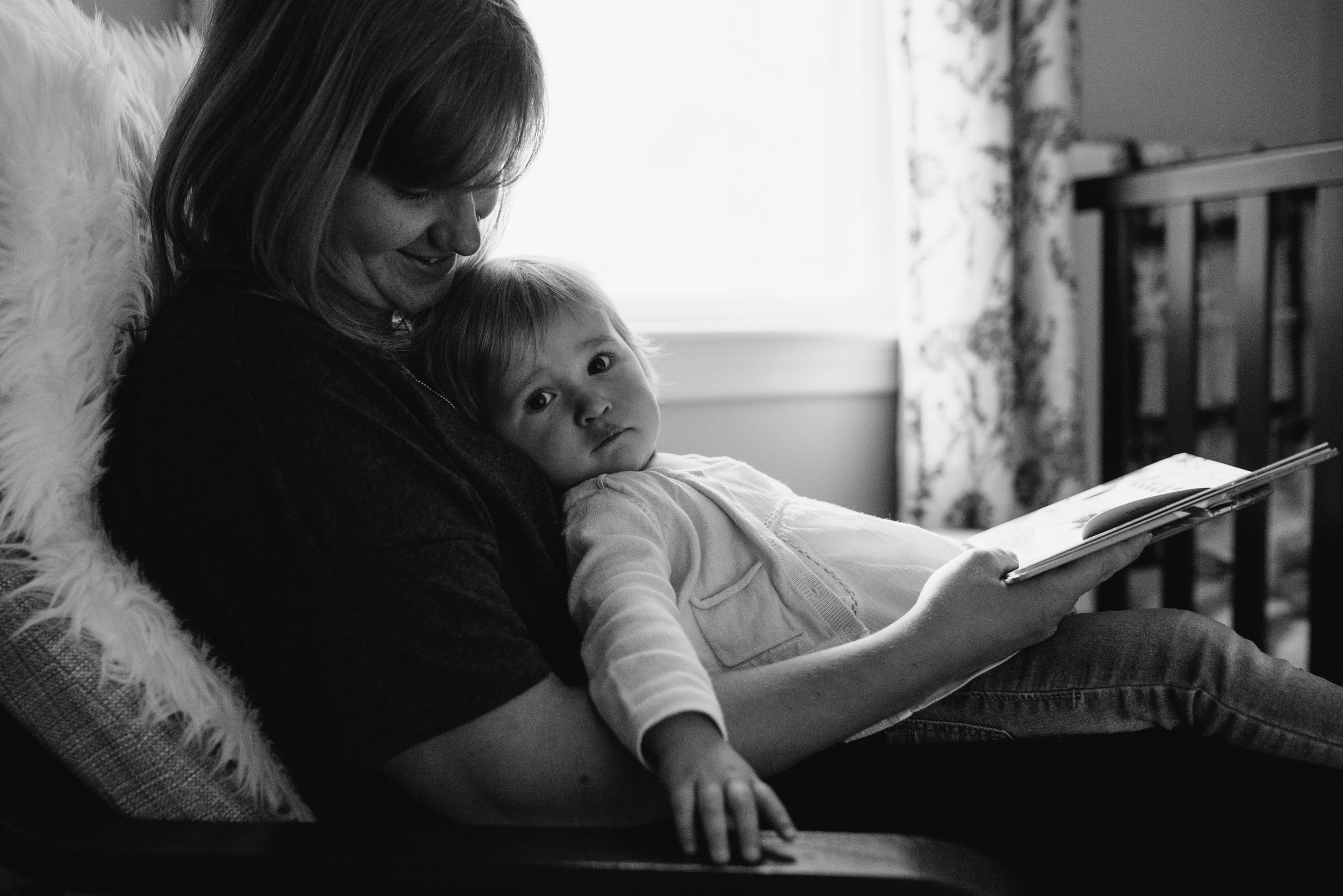 1 year old baby girl sitting in mom's lap reading book - Stouffville lifestyle photography