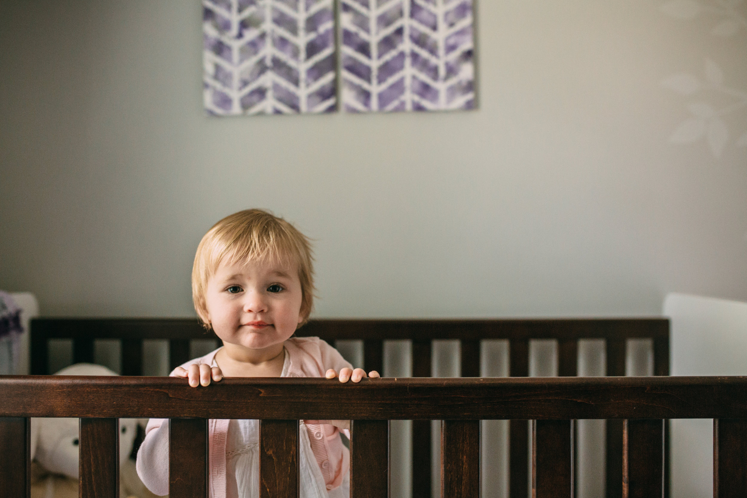 1 year old baby girl standing looking over side of crib at camera - Newmarket child photography