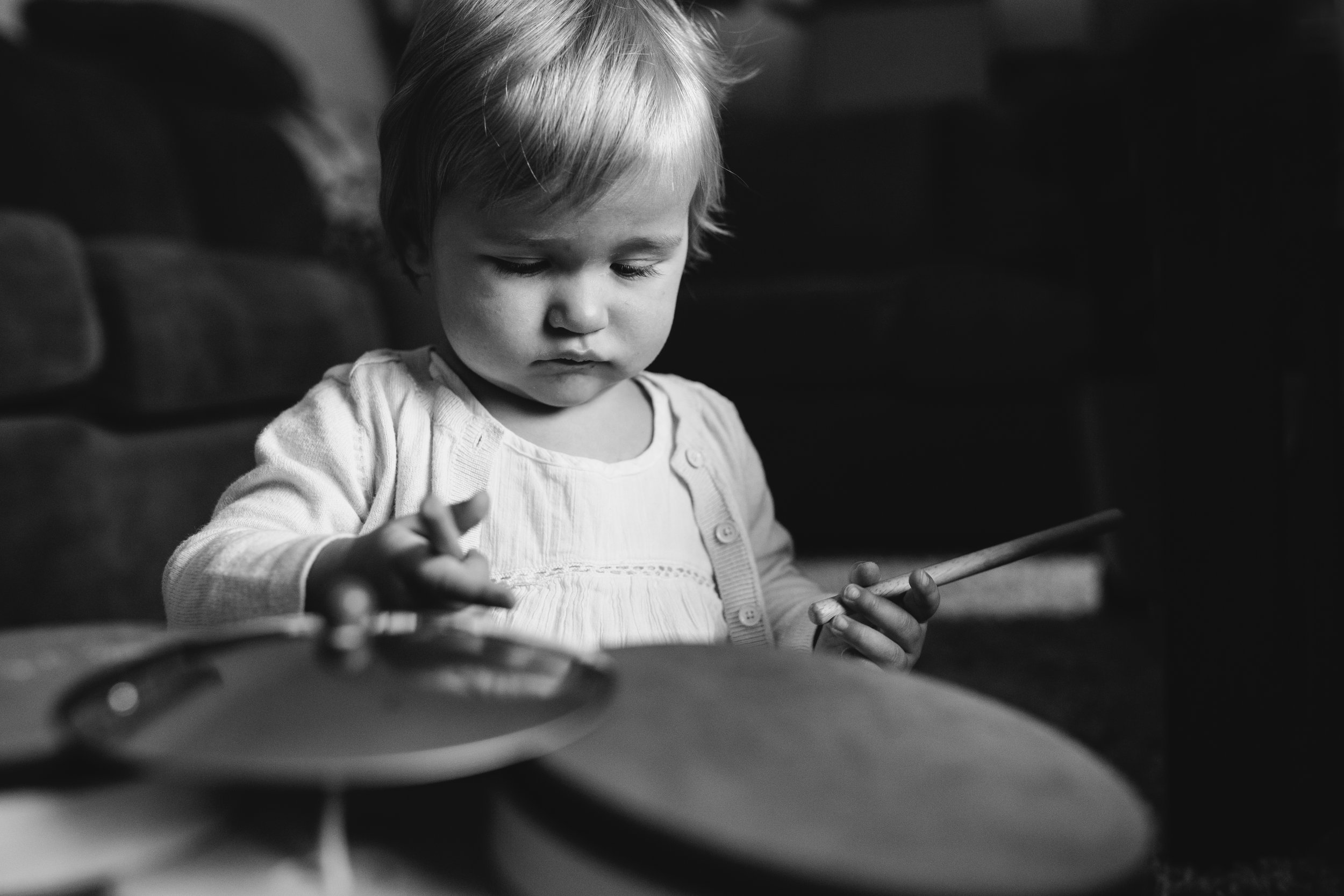 1 year old baby girl playing with toy drum set - Uxbridge child photography
