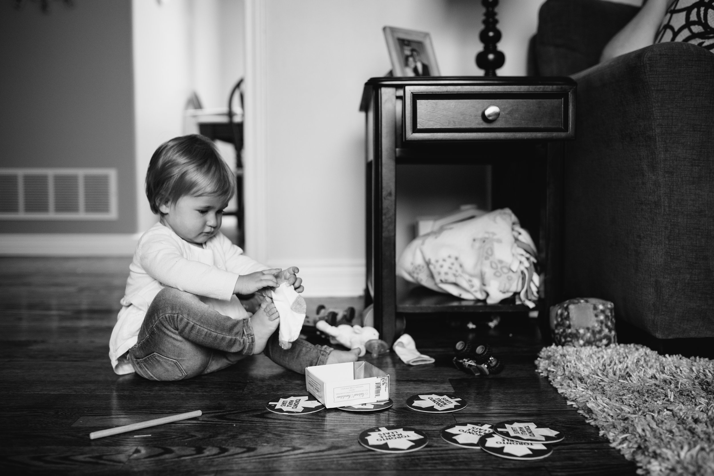 1 year old baby girl sitting on floor trying to put on sock - Stouffville child photos