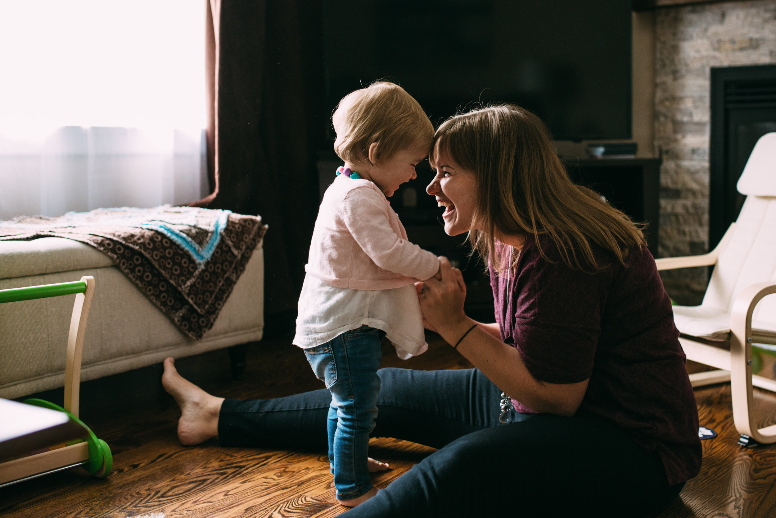 1 year old baby girl dancing and laughing with mom in living room - Newmarket in-home photography