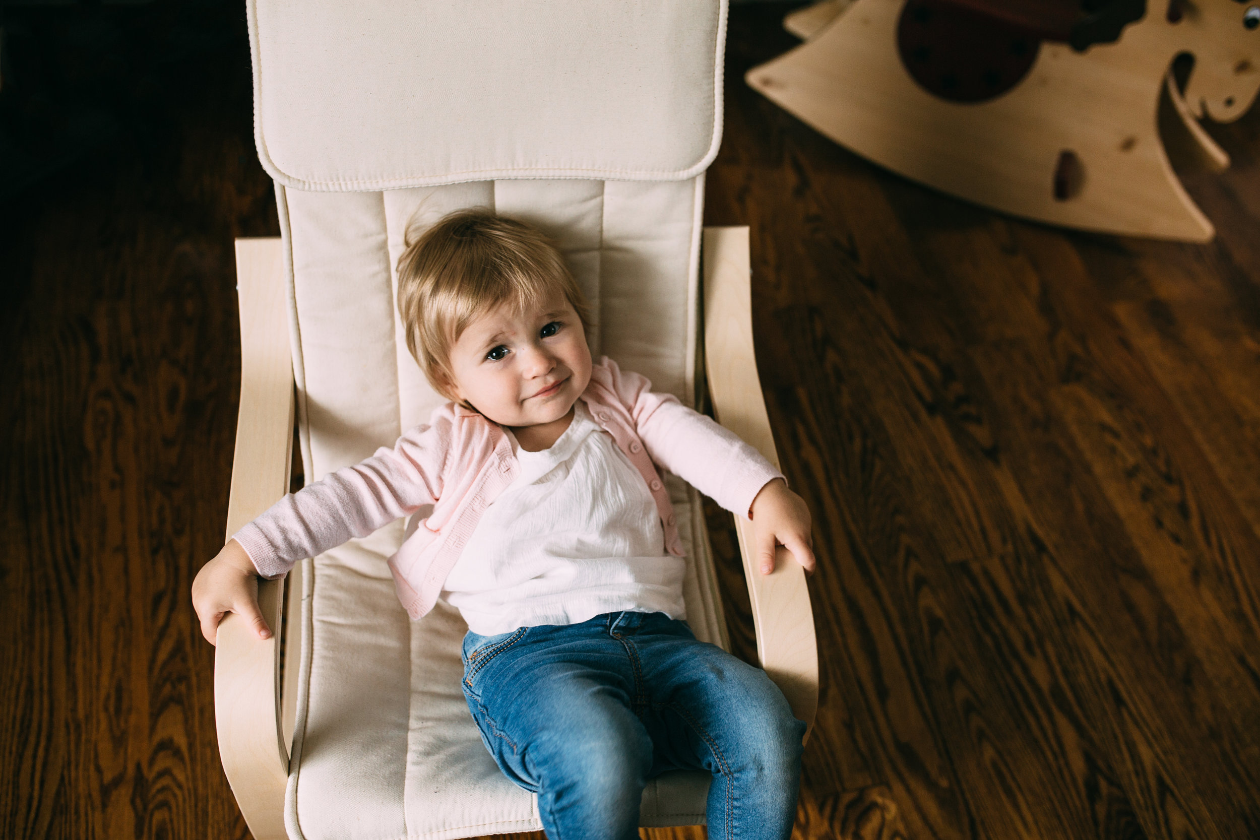 1 year old toddler girl sitting in cream chair looking at camera - Uxbridge child photography