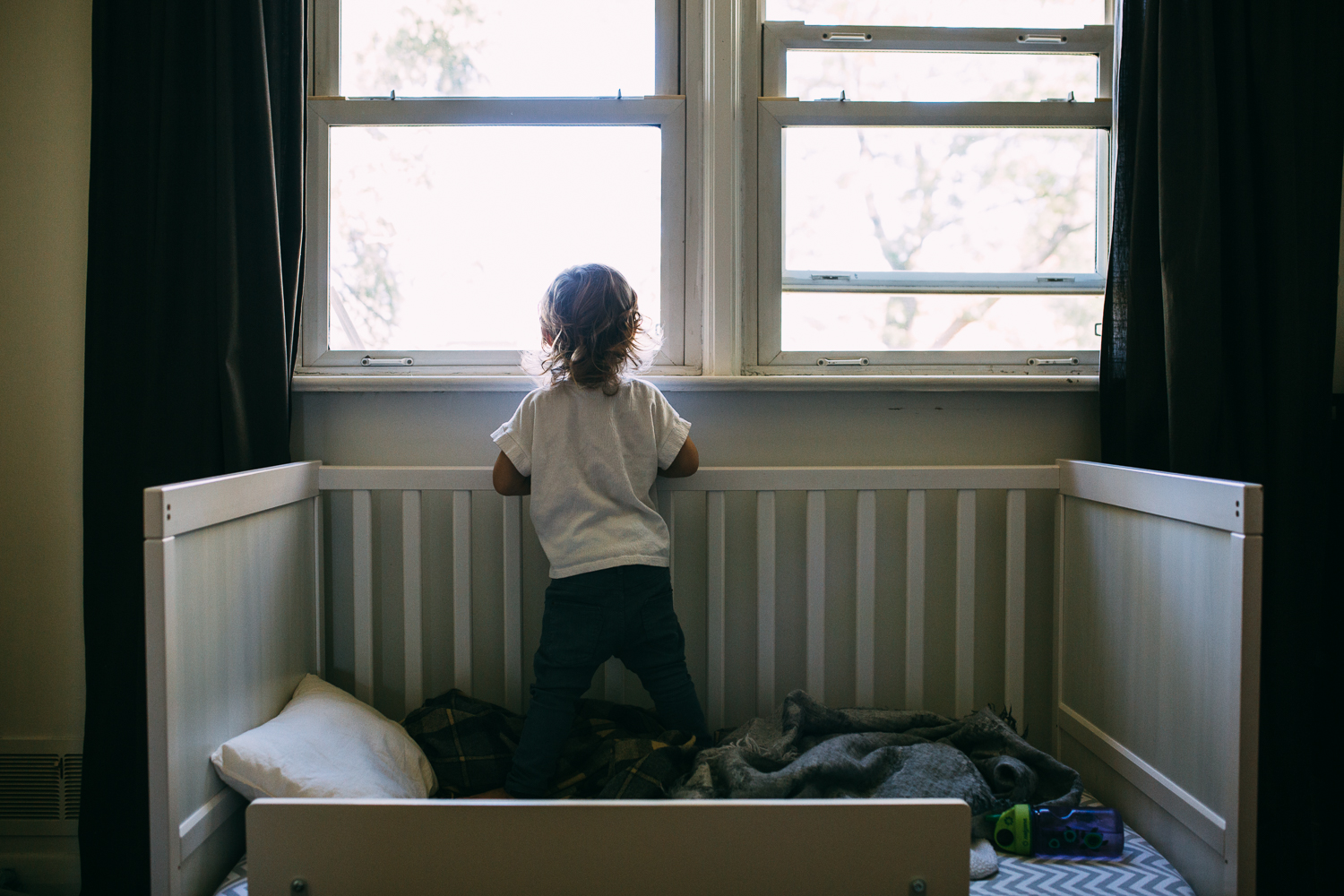 3 year old toddler boy standing in crib and looking out window - Stouffville family photography
