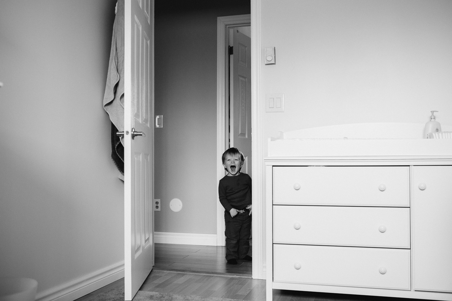2 year old toddler boy smiling in doorway to nursery - Markham family photos
