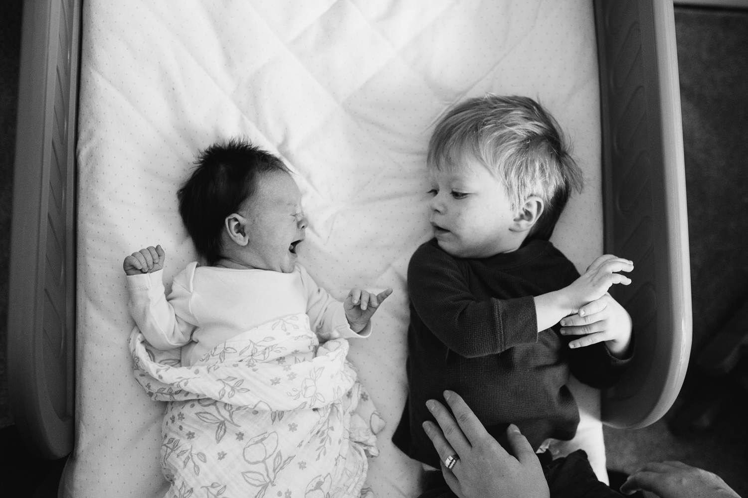 toddler big brother lying on bed with crying newborn baby sister - newmarket family photos