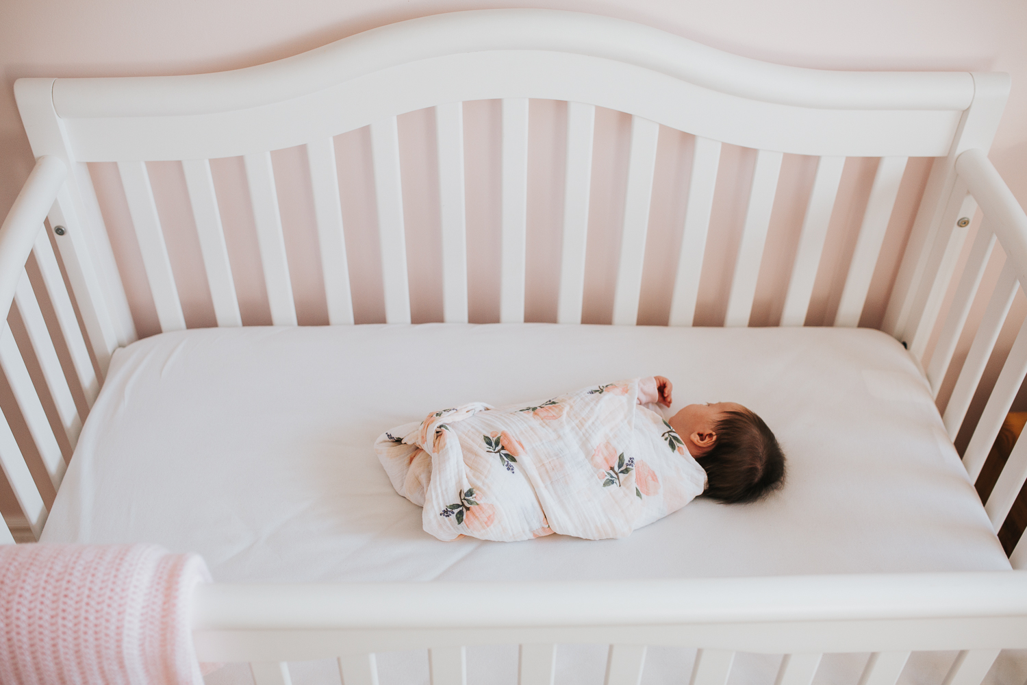 1 month old swaddled baby girl sleeping in crib in pink nursery - Newmarket newborn photography
