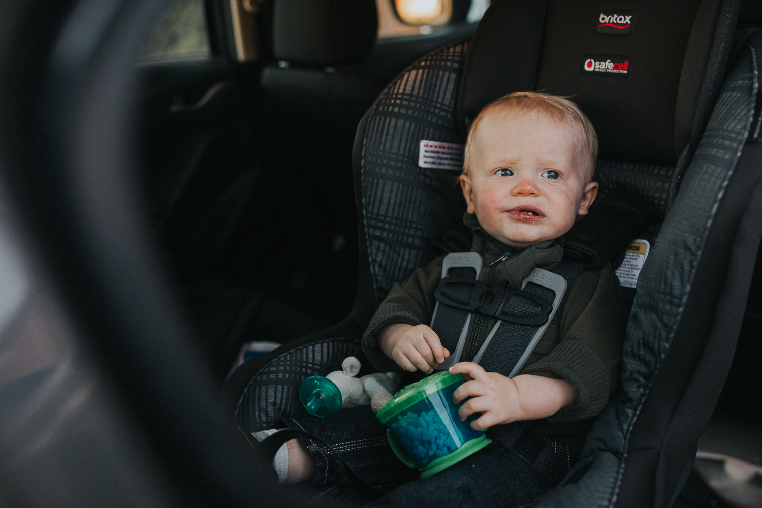 1 year old toddler boy eating snack in carseat - Stouffville child photography