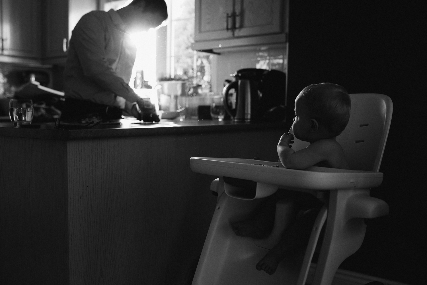 1 year old baby boy in highchair watching father in kitchen - Uxbridge Lifestyle photography