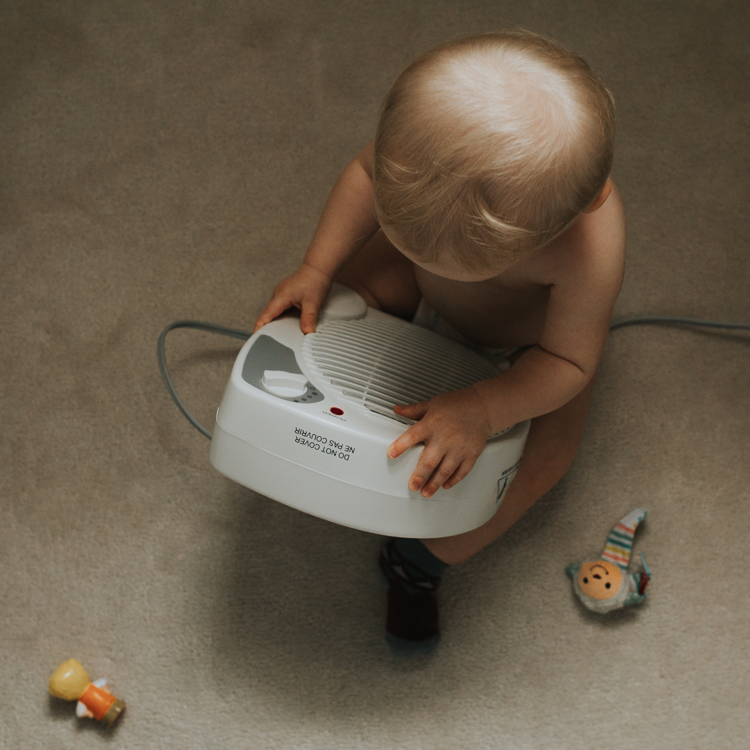 1 year old toddler boy sitting on floor playing with fan - Newmarket child photograph