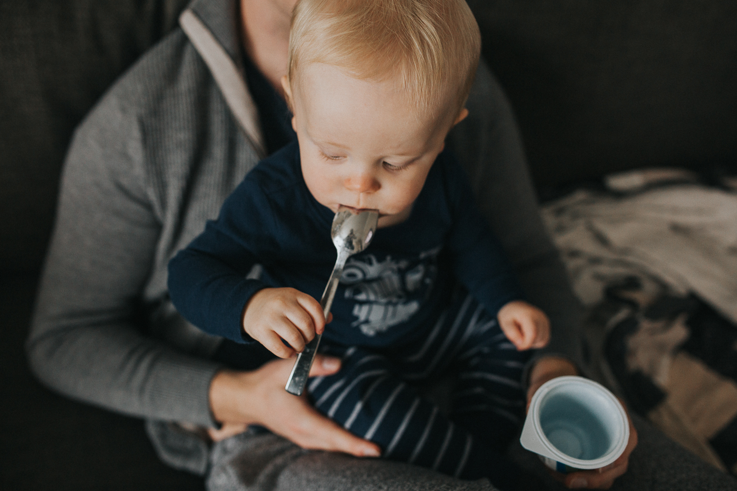 1 year old toddler boy eating yogurt with spoon on couch with father - Stouffville child photography