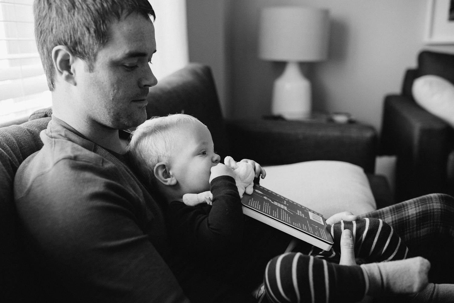 1 year old toddler boy sitting on dad's lap with book - Newmarket in-home photos