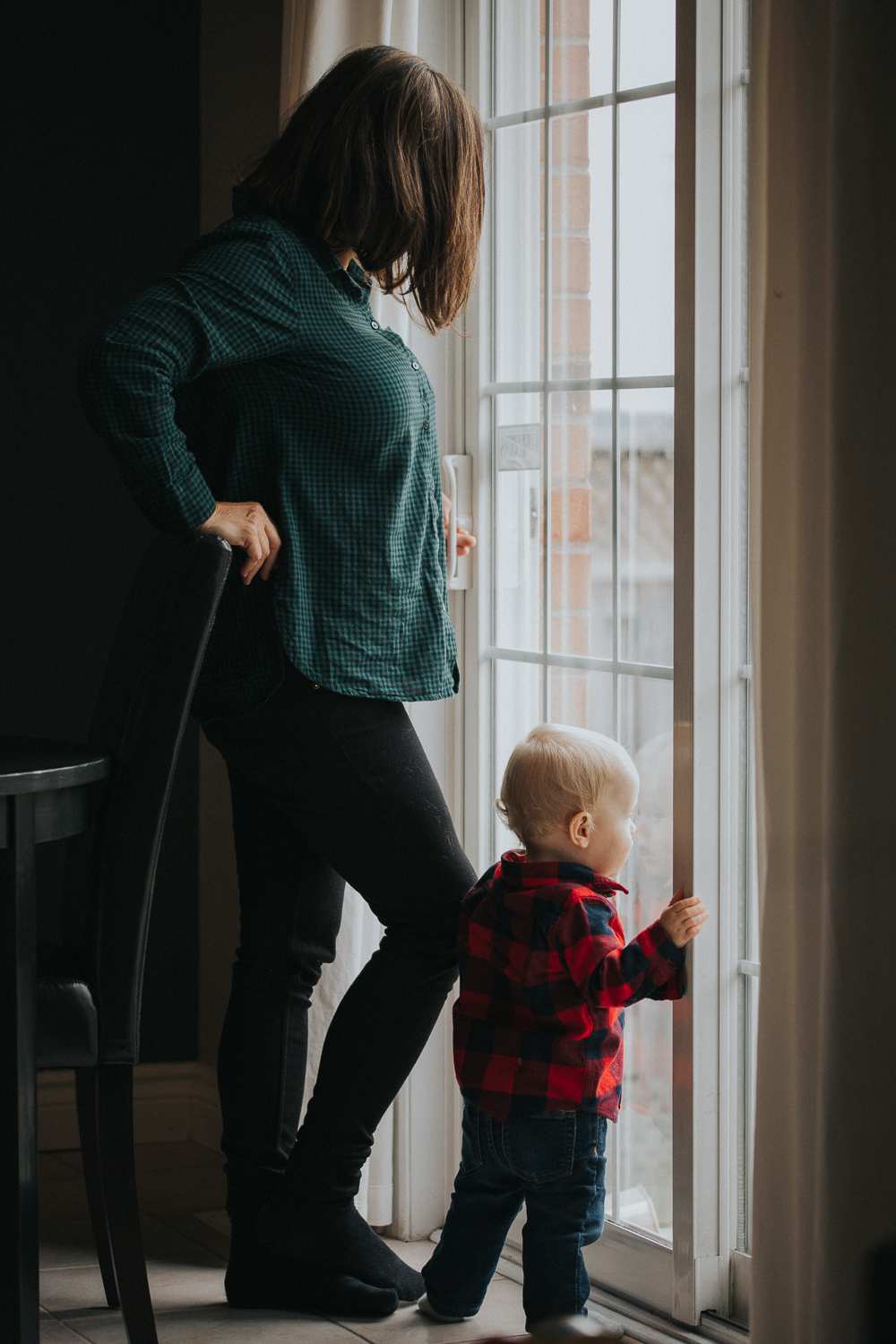 1 year old toddler boy in red shirt looking out window with grandma - Stouffville child photography