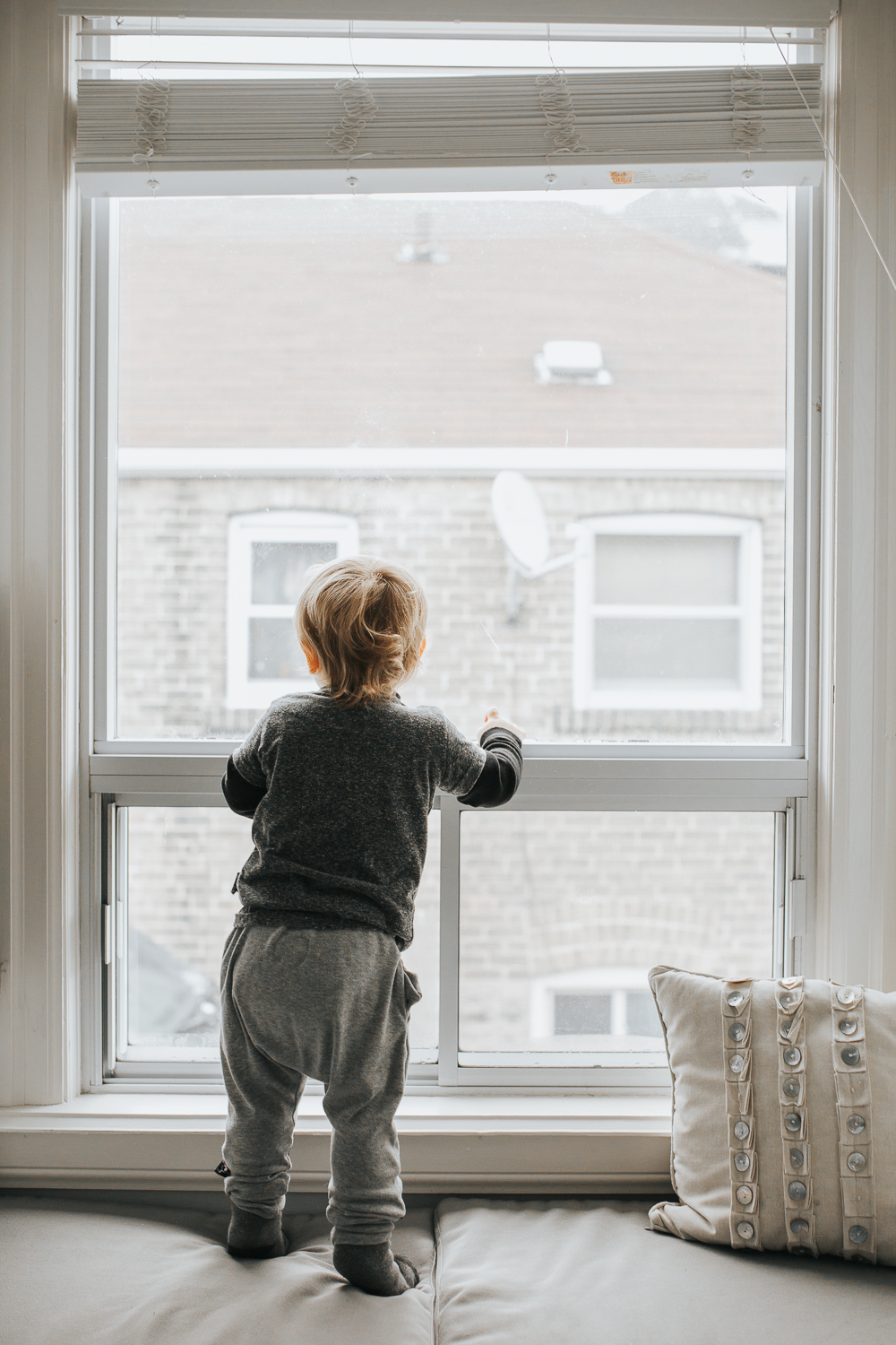 2 year old toddler boy looking out winder {Toronto Family Photographer}