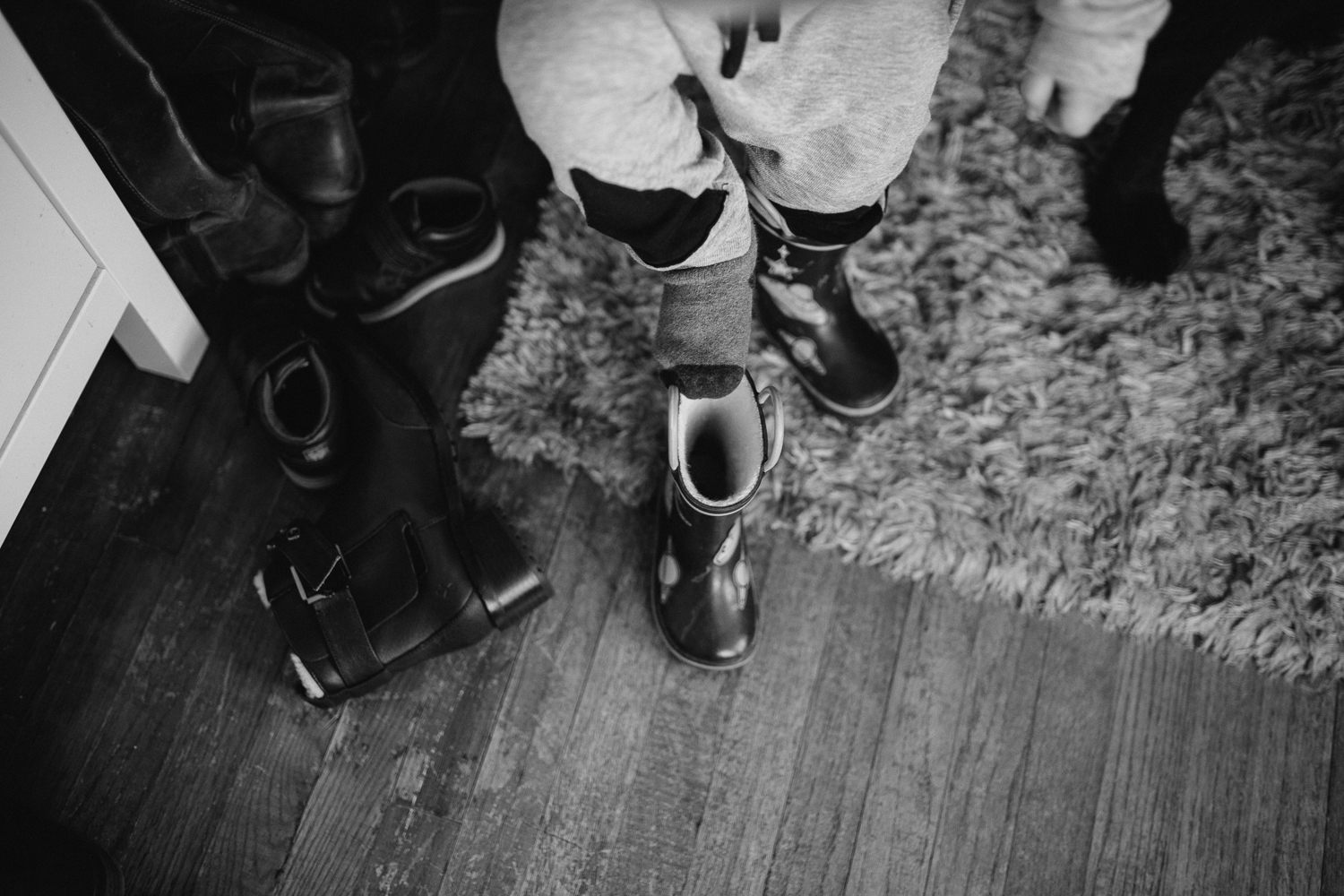 2 year old toddler boy putting boot on {Toronto Family Photographer}