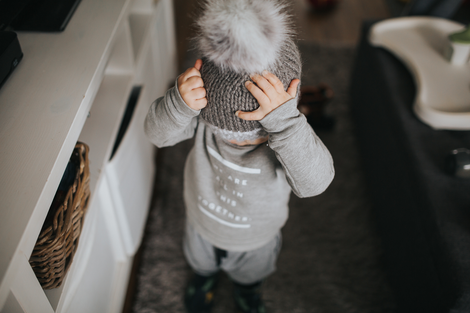 2 year old toddler boy putting hat on {Toronto Family Photographer}