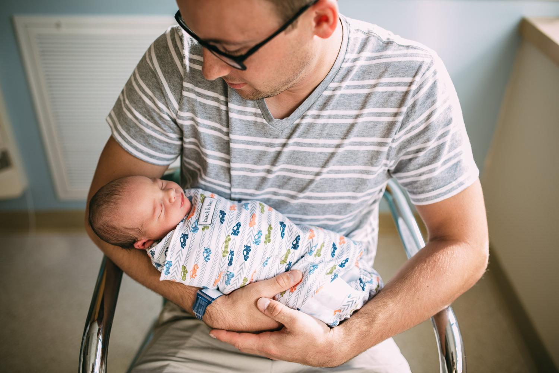 new dad holding newborn baby boy in hospital - Newmarket fresh 48 photographer