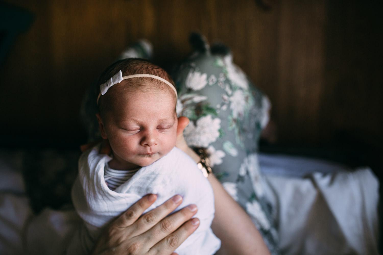 newborn baby girl asleep in mother's arms - Uxbridge in-home photos