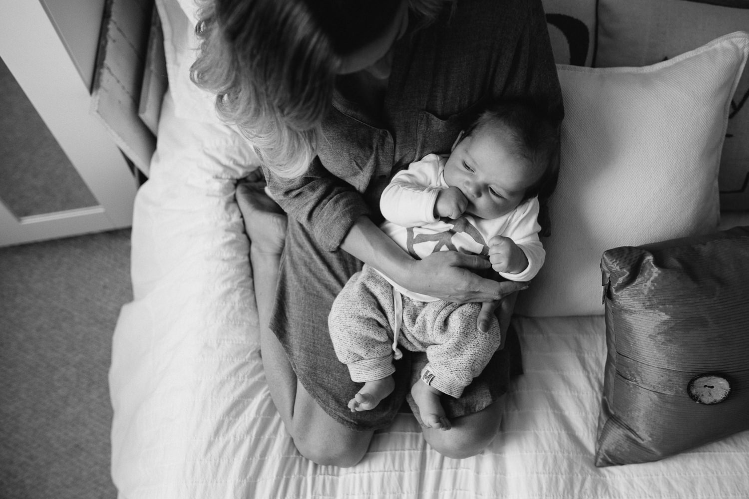 2 month old baby boy lying on moms legs in bedroom - Stouffville lifestyle photography