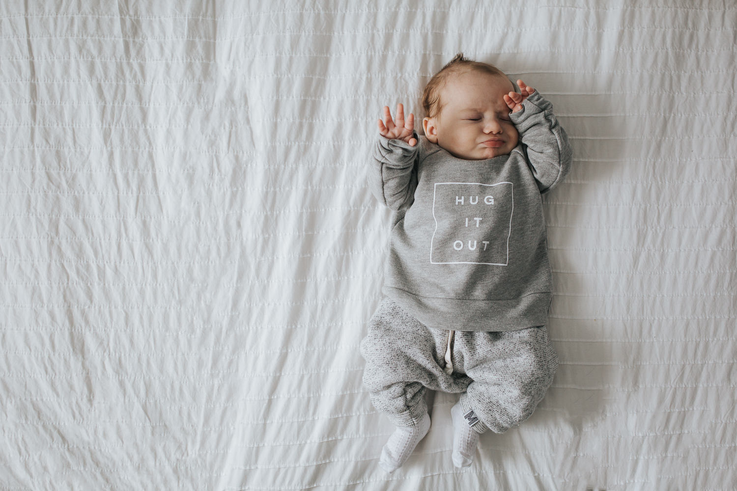 2 month old baby boy rubbing eyes lying on bed - Toronto baby photos