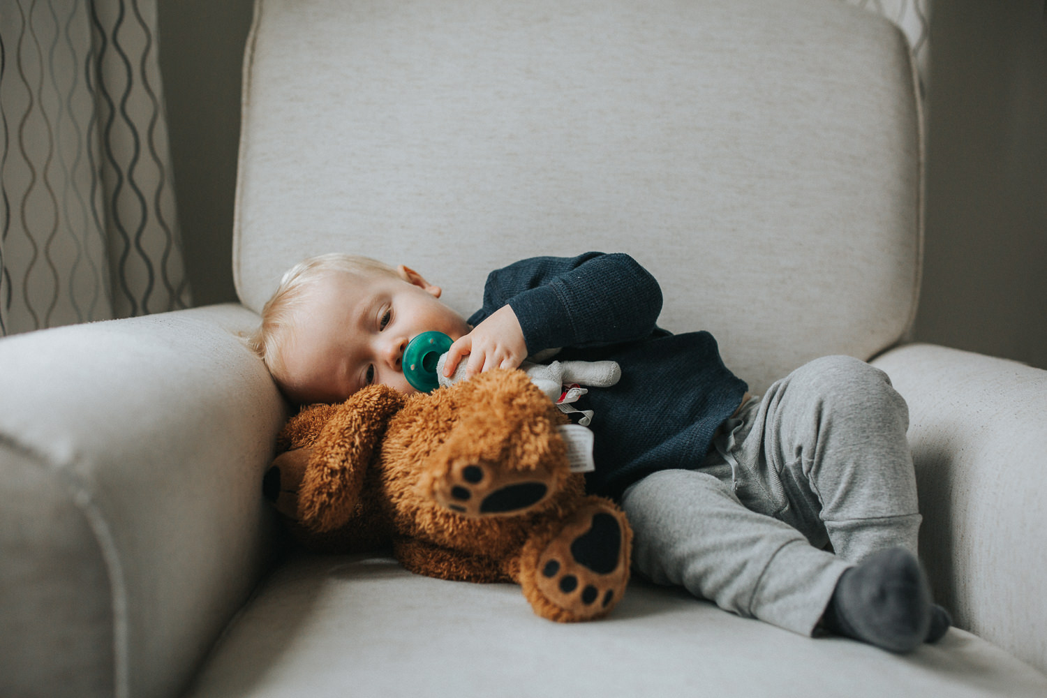 1 year old toddler boy lying on chair with stuffed bear - Newmarket lifestyle photography