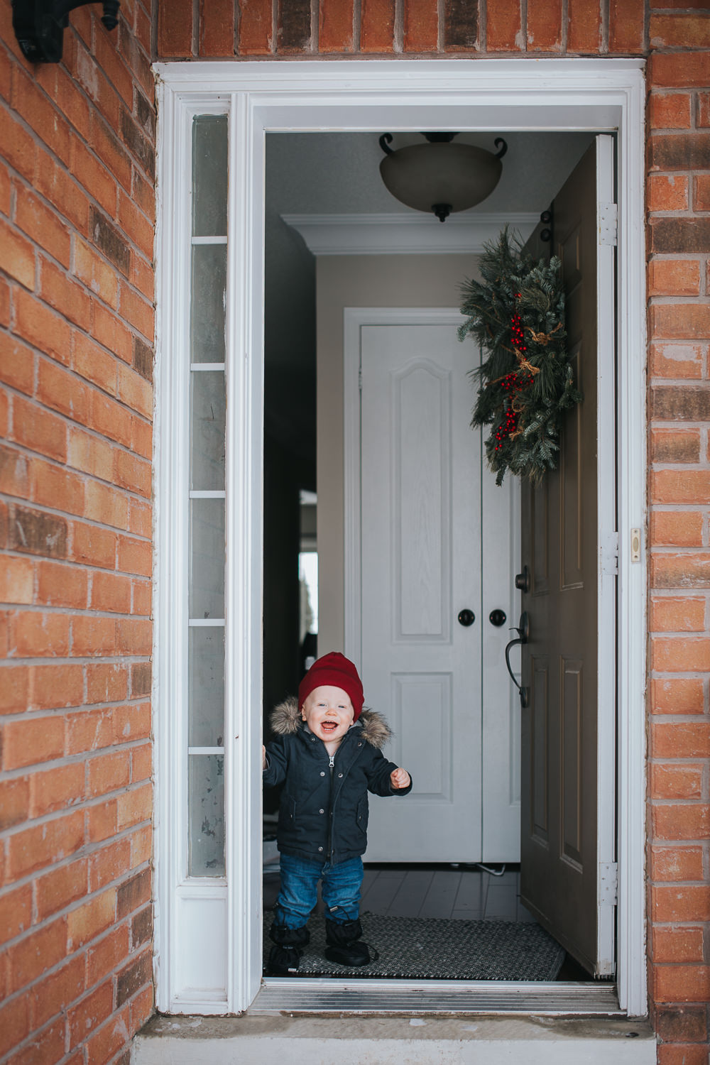 1 year old baby boy wearing parka and red hat standing in doorway - uxbridge child photographs