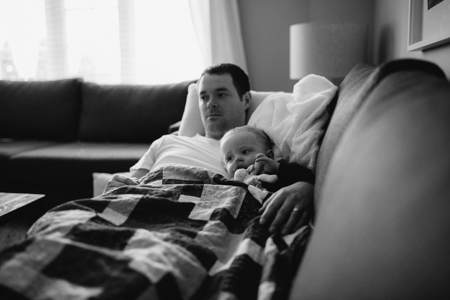 1 year old toddler boy lying with father on couch - Newmarket lifestyle photos