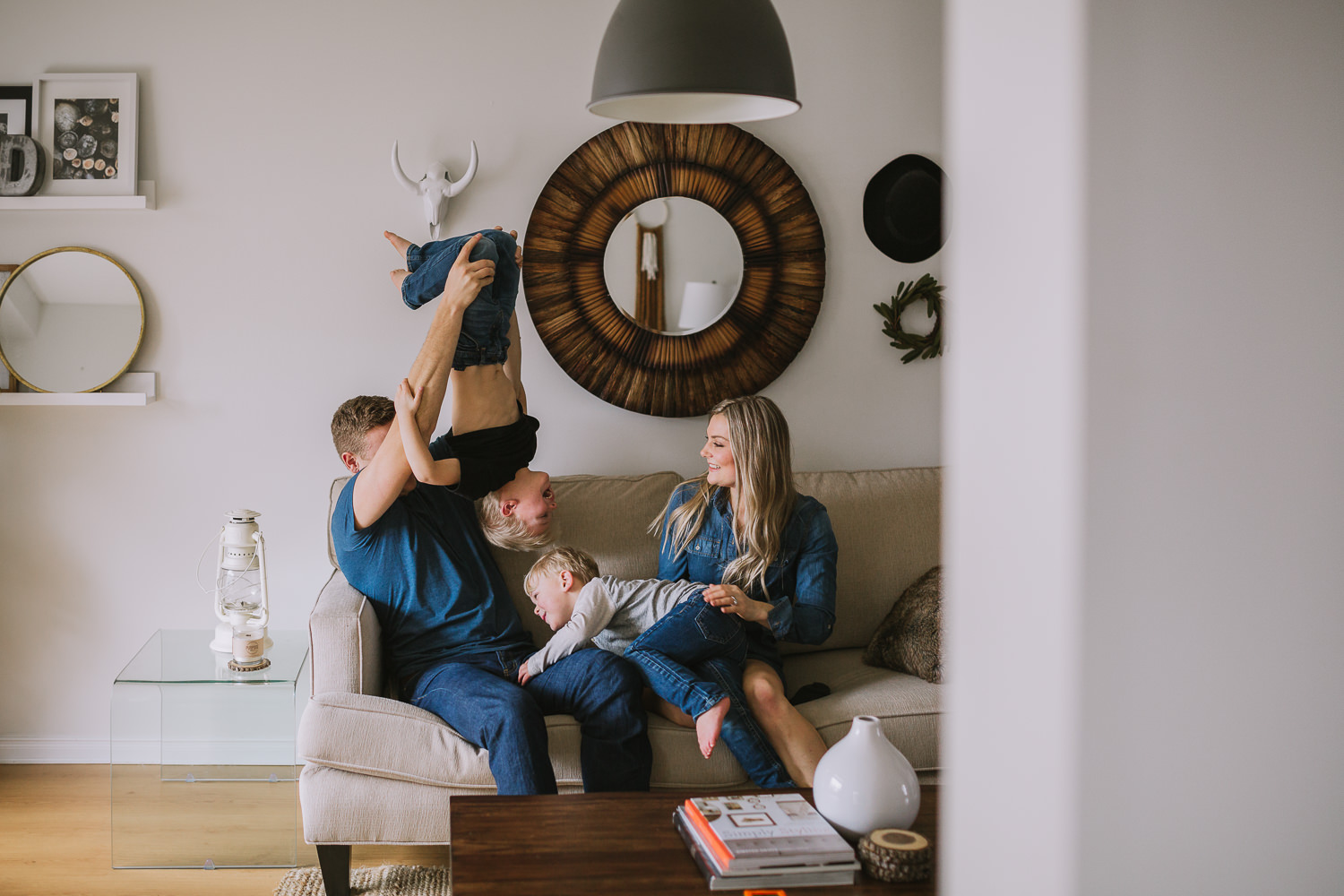 family of four with 2 blonde boys playing on couch - Stouffville child Photography
