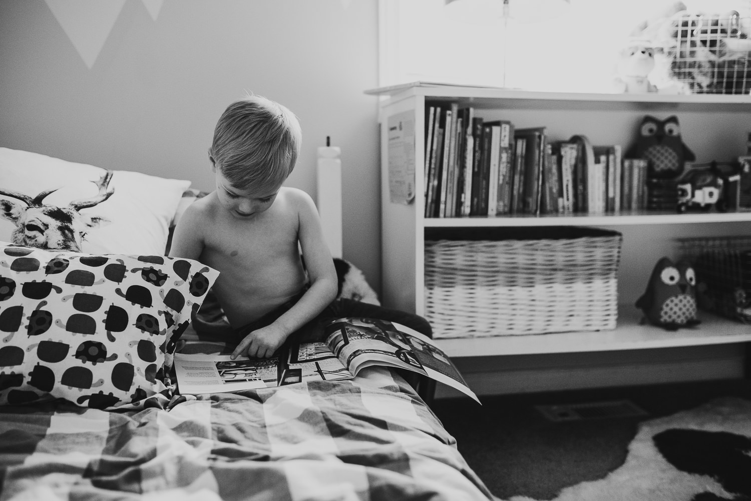 4 year old bot reads book while sitting on bed - Newmarket lifestyle photos