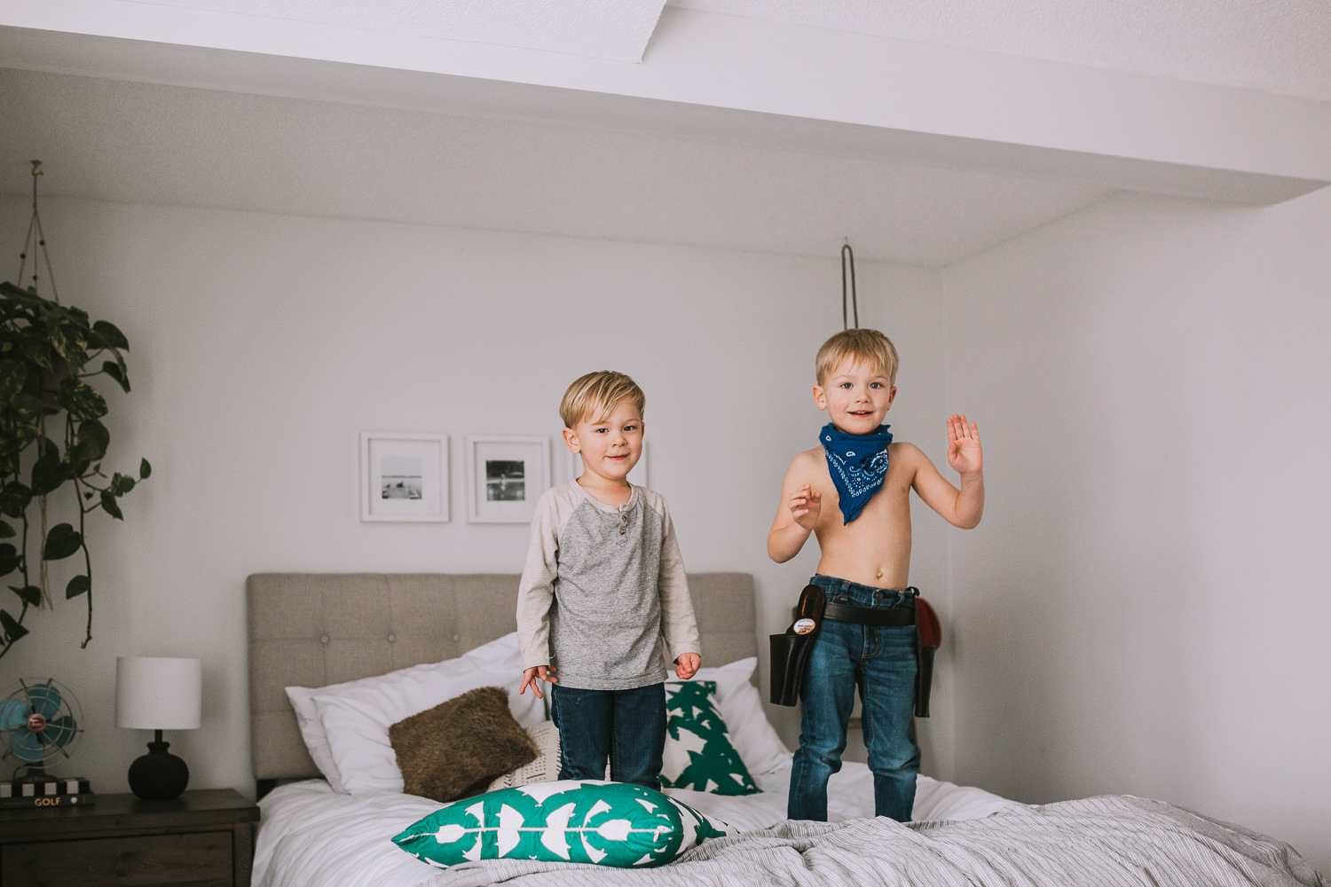 2 young blonde brothers standing on parents bed - Uxbridge lifestyle photography