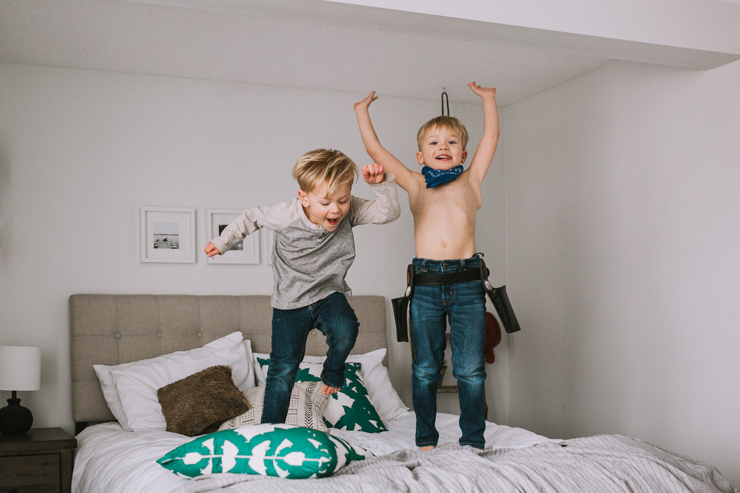 2 young blonde brothers jumping on parents bed - Newmarket lifestyle photography