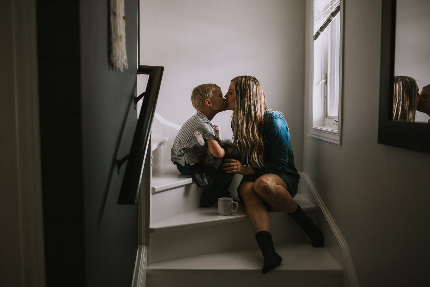 Mom kisses 4 year old blonde son holding pet cat while sitting on stairs - Stouffville child photography