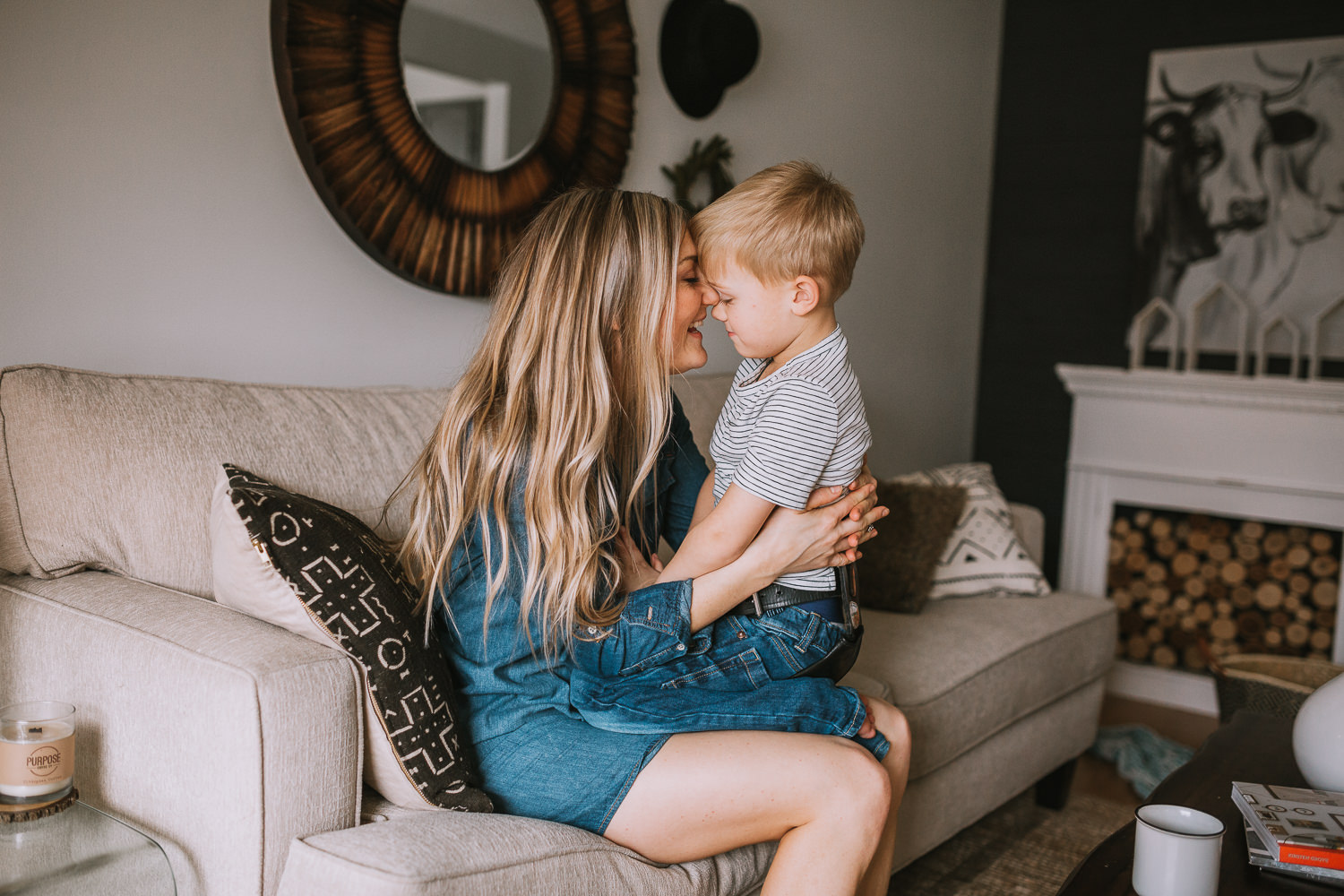 mom with long blonde hair holds 4 year old son in lap touching foreheads - Stouffville child photography
