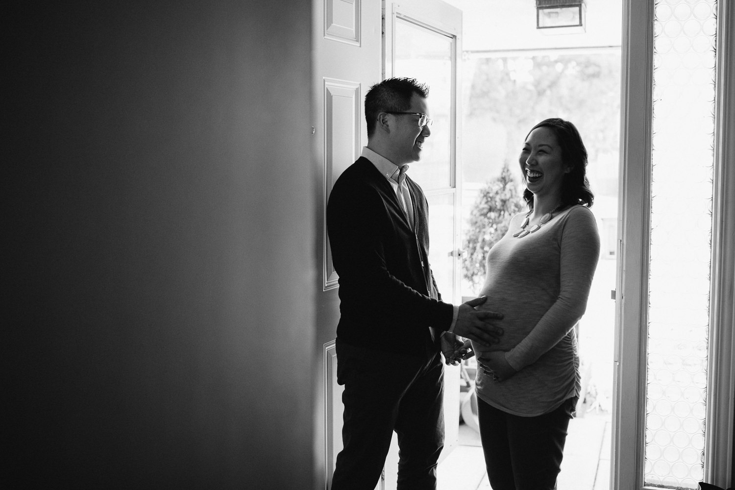 husband and pregnant wife laughing in doorway - Newborn Lifestyle Photography