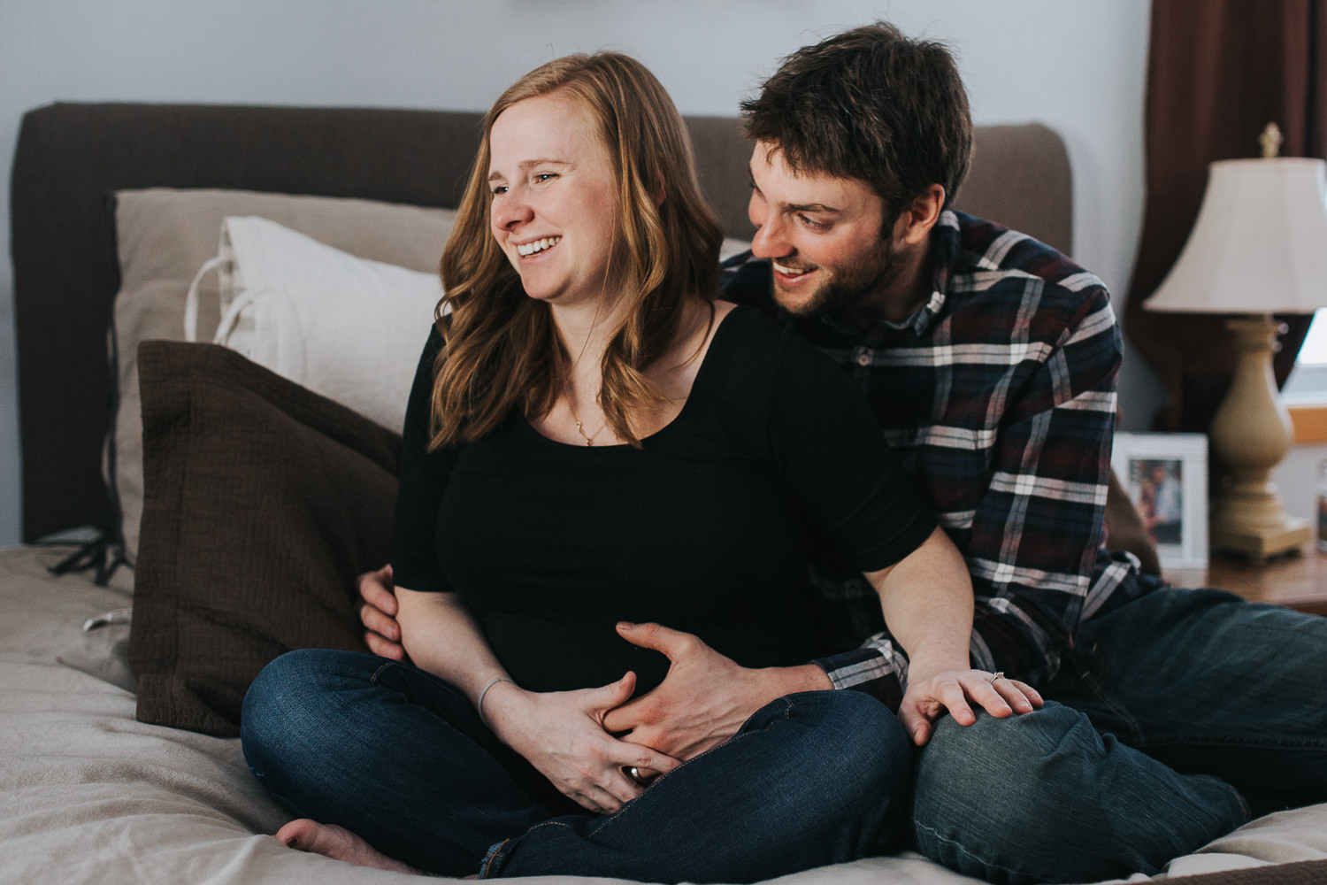 pregnant wife and husband laughing on bed - Markham lifestyle photography