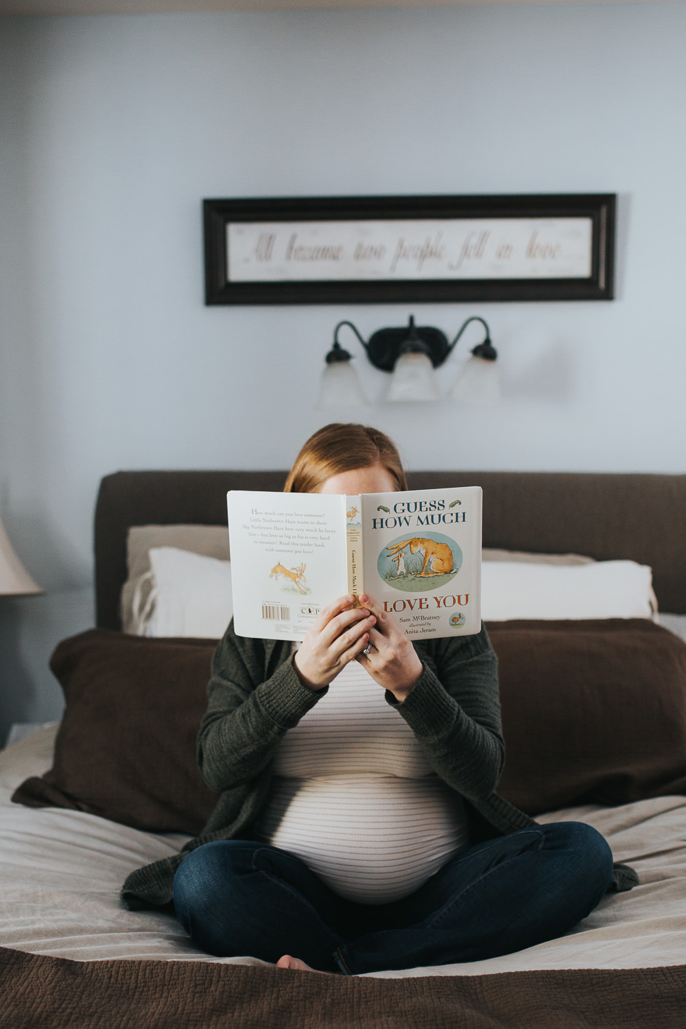 pregnant mom to be sitting cross legged on bed holding book - newmarket in-home photography