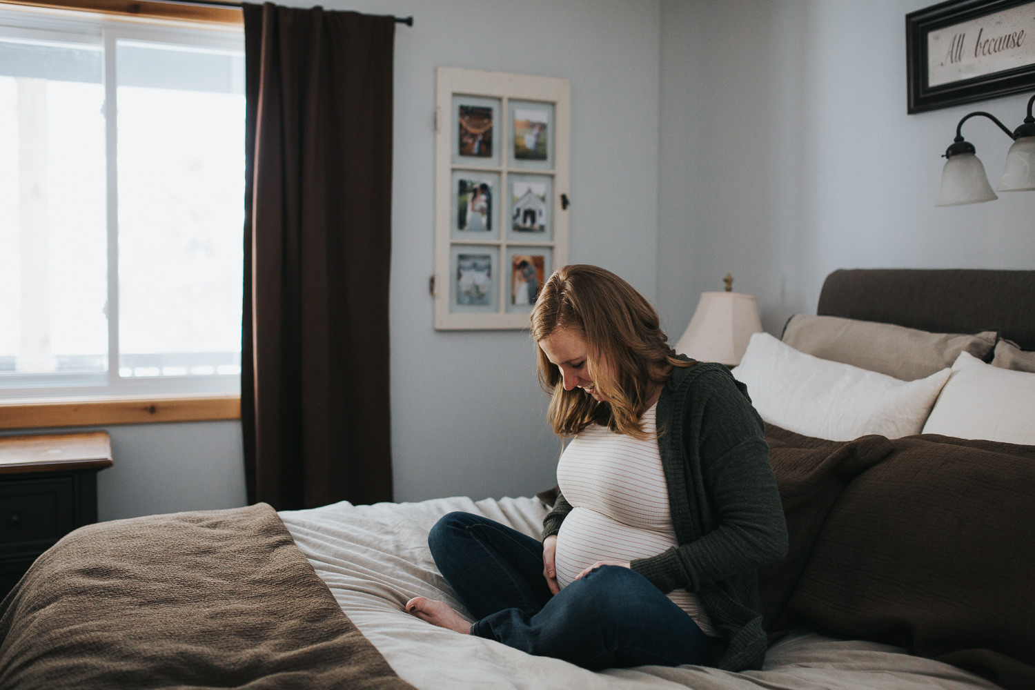 pregnant mom to be sitting on bed holding baby bump - uxbridge in-home photography