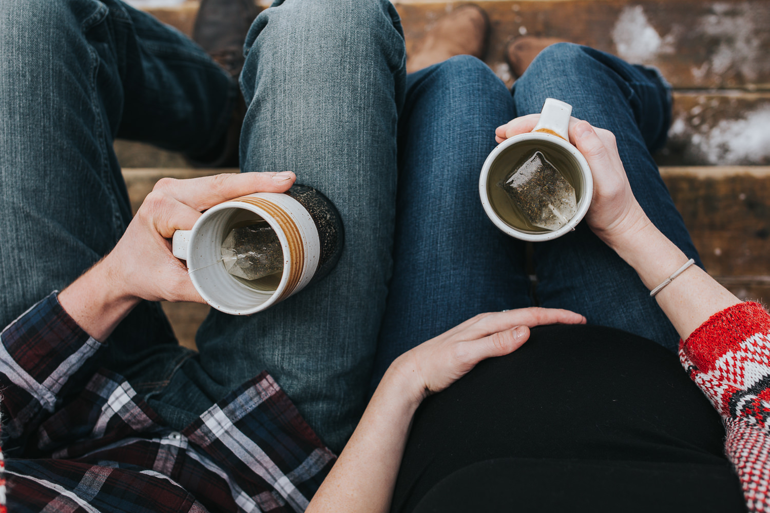 husband and wife holding mugs of tea, mom's hand on baby belly - Newmarket lifestyle photos