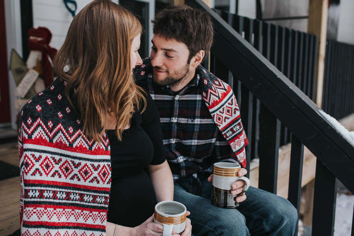 parents to be sitting on front porch steps wrapped in blanket looking at one another  - Stouffville lifestyle photography