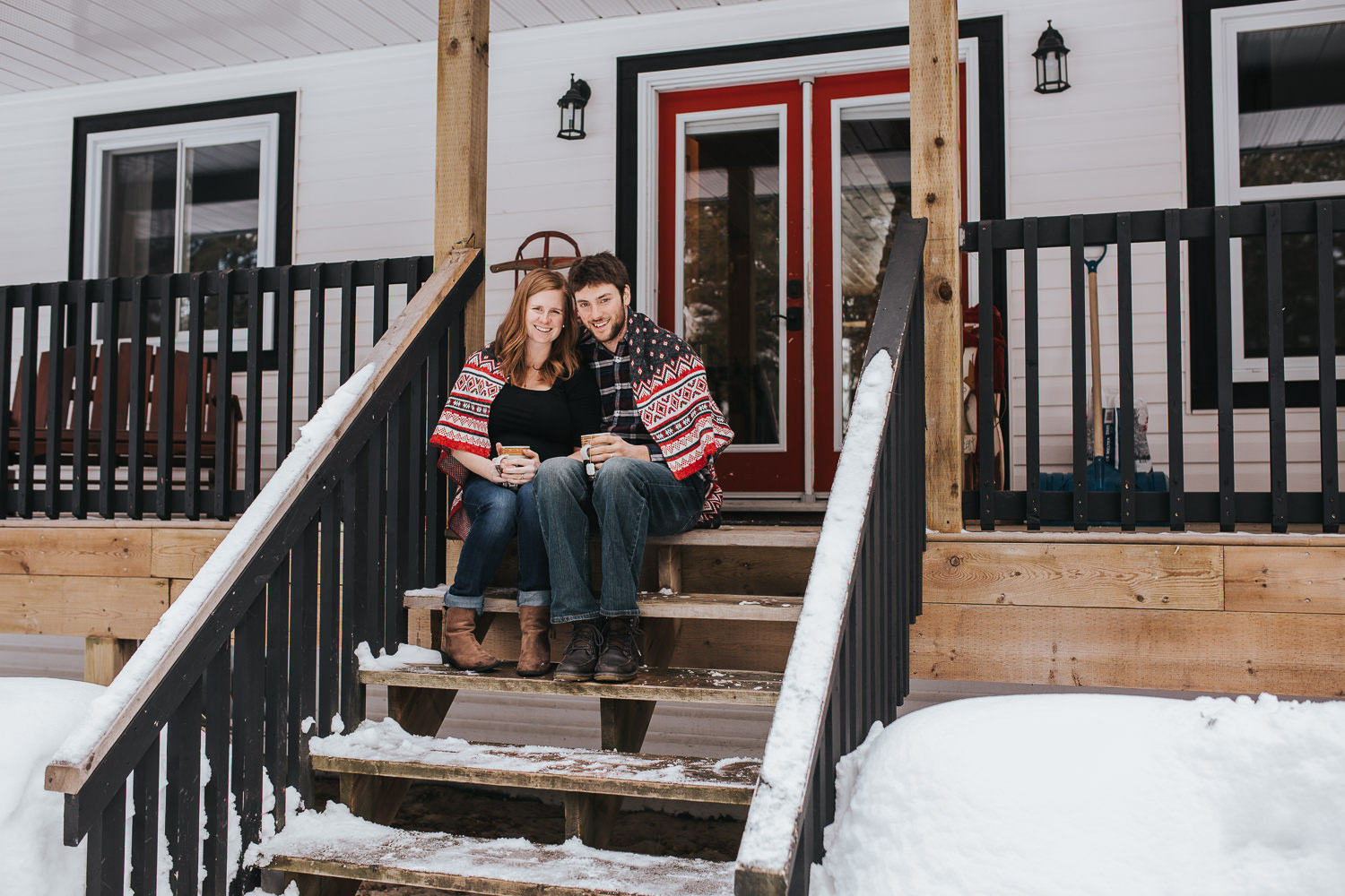 parents to be sitting on front porch steps wrapped in blanket looking at camera  - Markham lifestyle photos